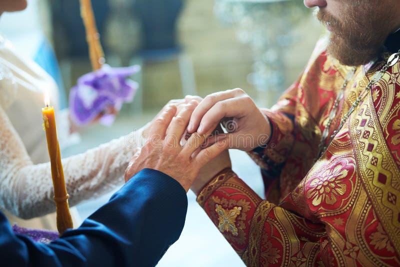 新郎和新娘婚姻的订婚仪式的在东正教里 免版税库存照片