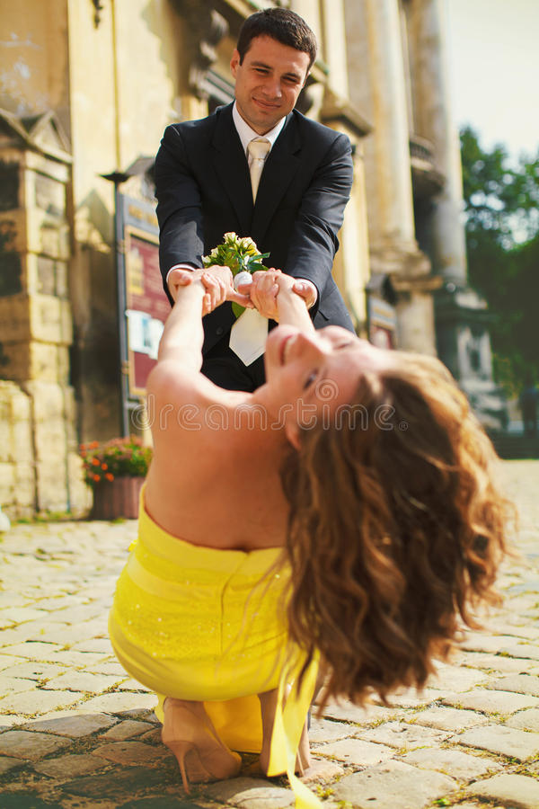 新郎和新娘演奏在街道上的傻瓜 免版税库存图片