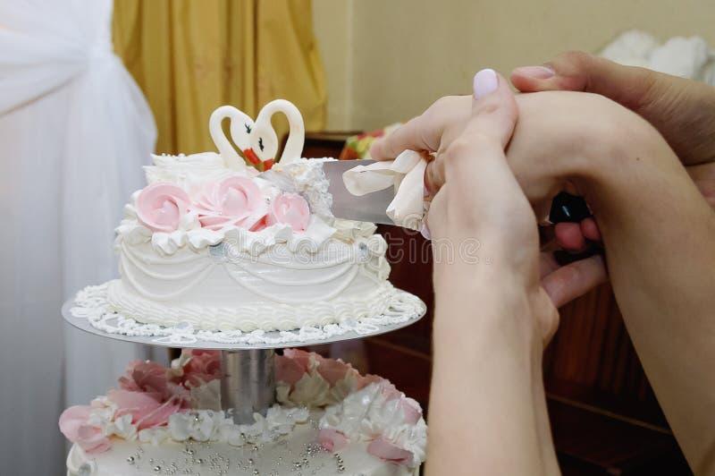 新郎和新娘的手切了与刀子,特写镜头的婚宴喜饼 免版税库存图片