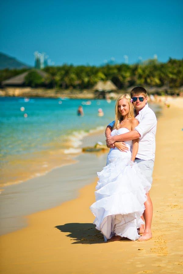 新郎在一个热的晴天拥抱海滩的新娘 免版税库存照片