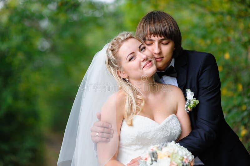 新郎在夏天公园拥抱步行的新娘 免版税库存图片