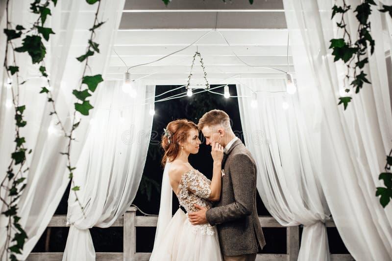 新郎在庭院里亲吻新娘嫩` s的面颊拥抱她 库存照片