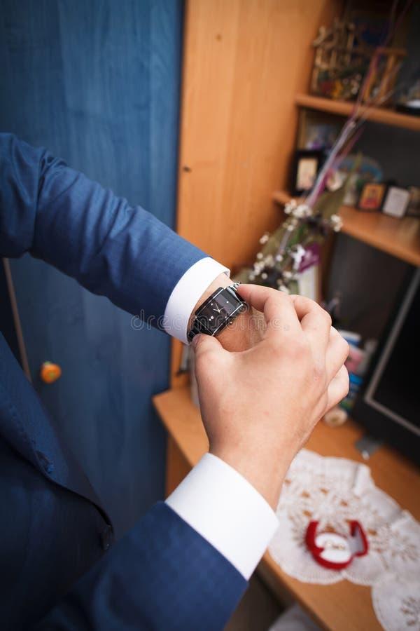 新郎在手表看 免版税库存照片