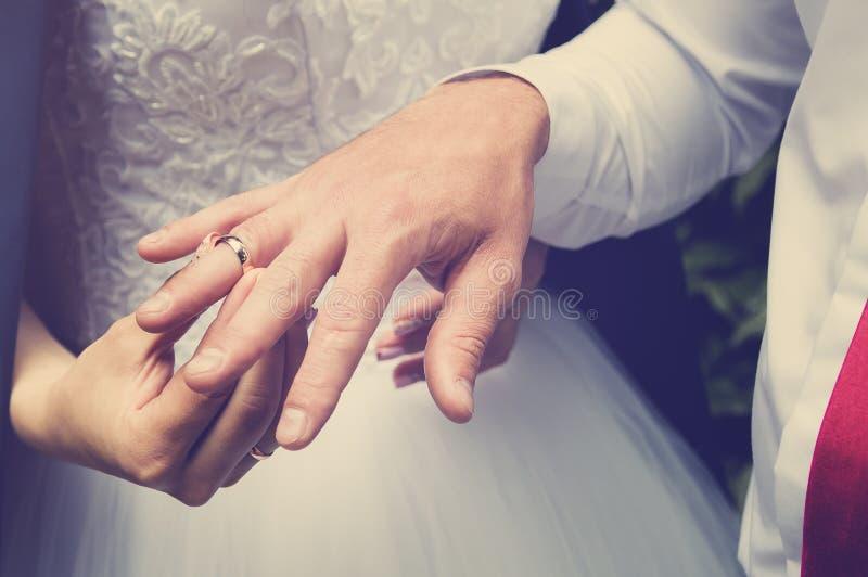 新郎在新娘上,手特写镜头的手指把圆环放 定调子仿照instagram样式 库存图片