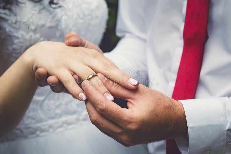 新郎在新娘上,手特写镜头的手指把圆环放 免版税库存照片