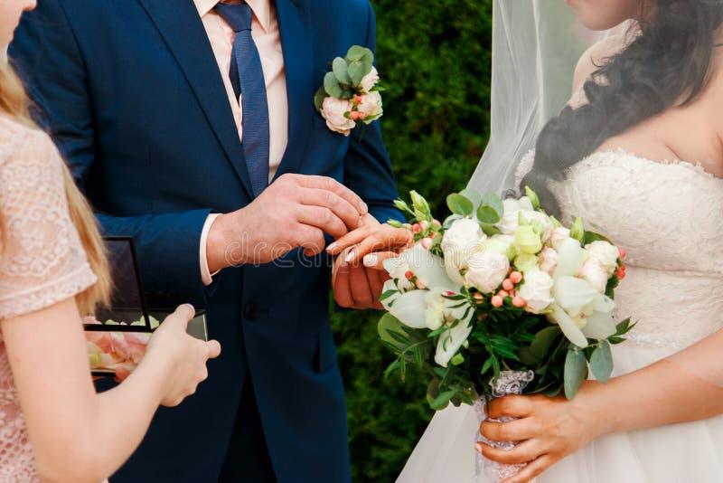 新郎在新娘的手指安置结婚戒指 库存照片
