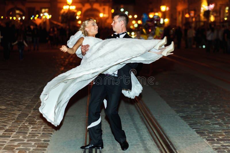 新郎在晚上旋转一新娘somewere在老城市 免版税库存图片