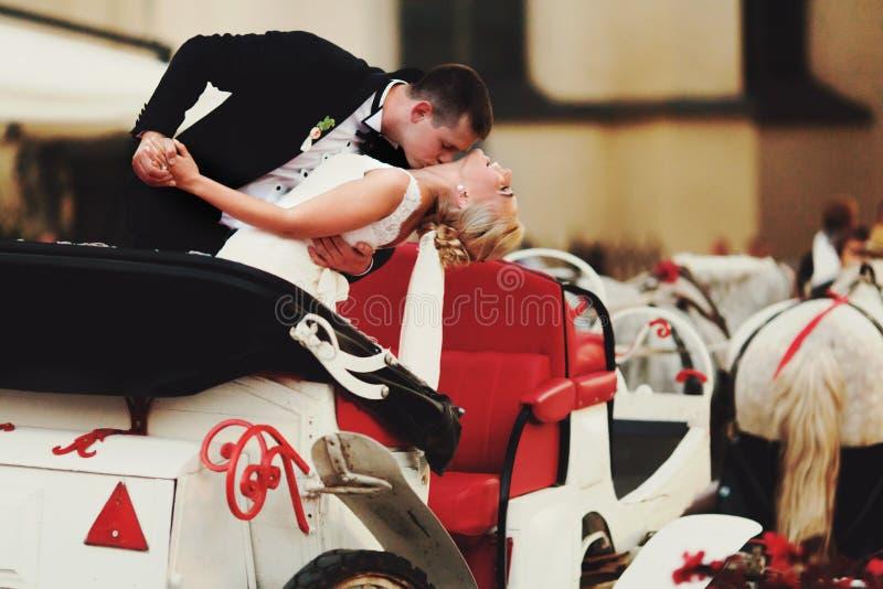 新郎在他的胳膊弯曲在举行她和身分的新娘在t 免版税图库摄影
