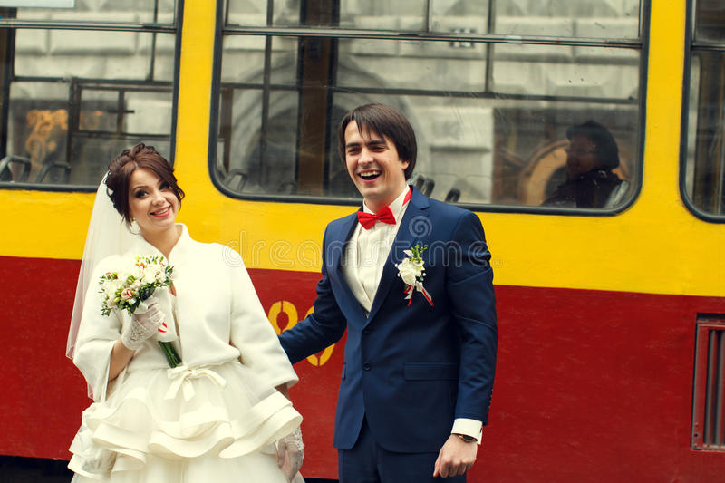 新郎微笑恳切地站立与在电车后的一个新娘 库存图片