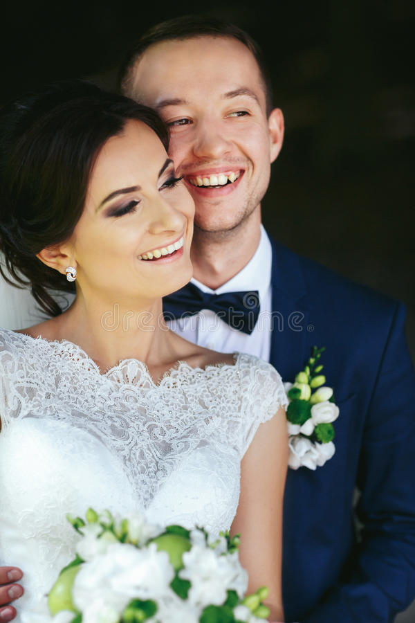 新郎微笑拿着他的胳膊的一个精美新娘 库存照片