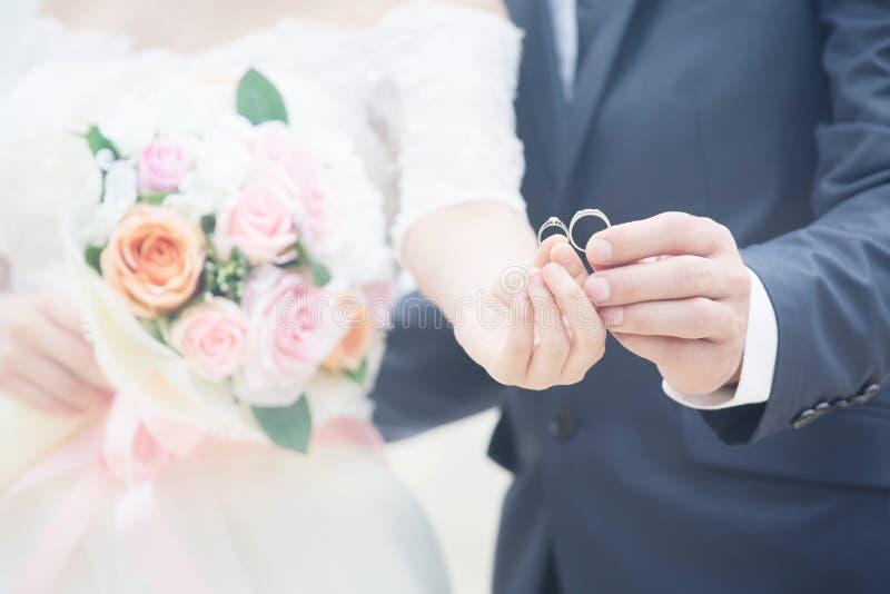 新郎手和新娘的关闭 年轻男性和女性夫妇与握手的展示结婚 免版税库存照片