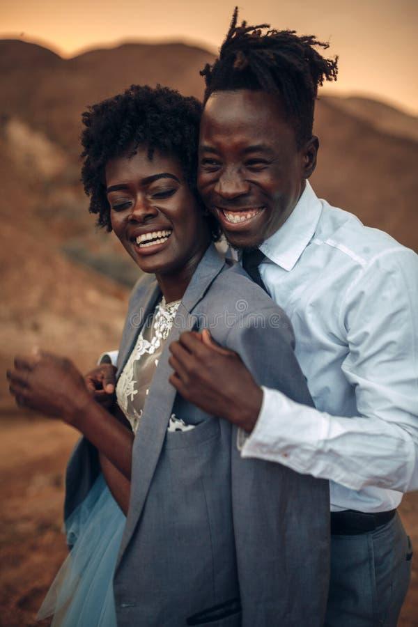 新郎拥抱在他的在峡谷的夹克打扮的他的新娘在日落a 图库摄影