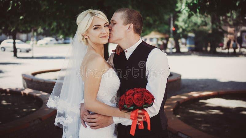 新郎拥抱并且亲吻面颊的新娘 免版税库存照片