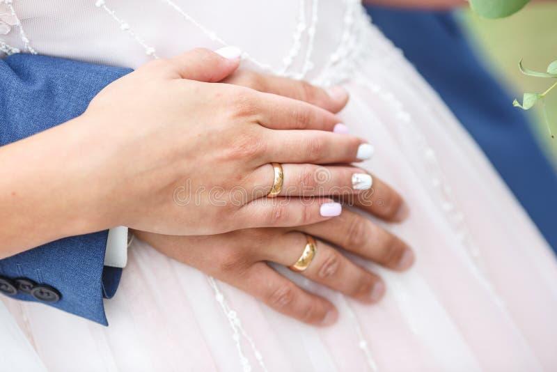 新郎拥抱新娘 在新婚的夫妇的手上的圆环 免版税图库摄影