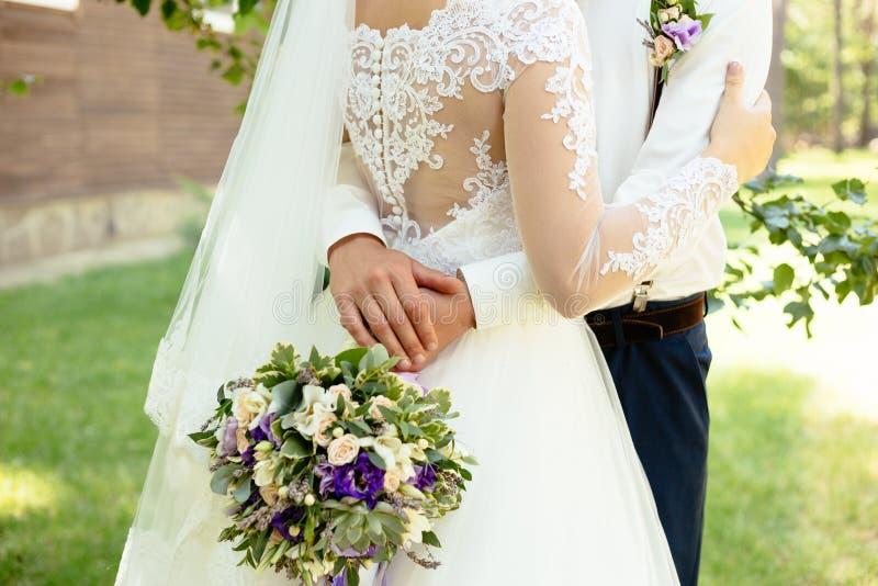 新郎拥抱白色的新娘与鞋带后面礼服 库存照片