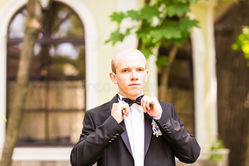 新郎拿着一条领带并且微笑 免版税库存图片
