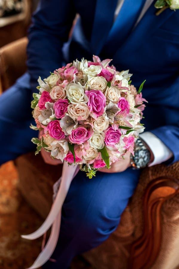 新郎拿着新娘的花束 o 图库摄影