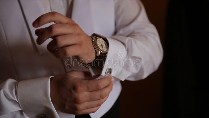 新郎握在领带的手,婚姻衣服 关闭一个手人怎么佩带白色衬衣和链扣 在白色的背景商业查出的人 库存照片