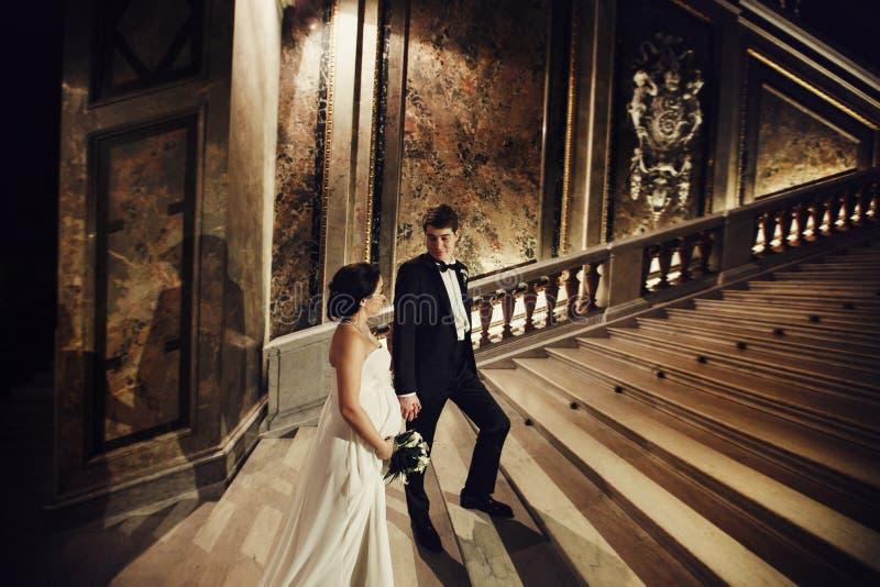 新郎握新娘站立在一老theatr的台阶的` s手 免版税库存照片
