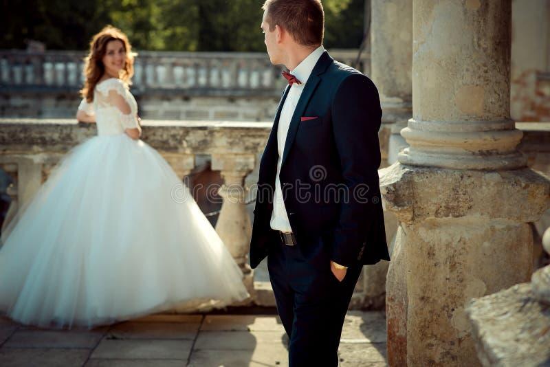 新郎注视着在他的肩膀站立他迷人的微笑的姜头发的新娘在的背景 库存照片
