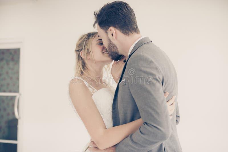 新郎画象有一起亲吻和拥抱在白色背景,愉快和微笑在订婚天,葡萄酒的新娘的定了调子 库存照片