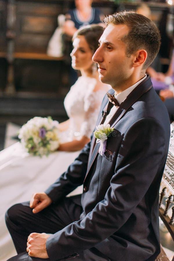 新郎的半身旁边画象坐椅子在婚礼期间在被弄脏的教会里 库存图片