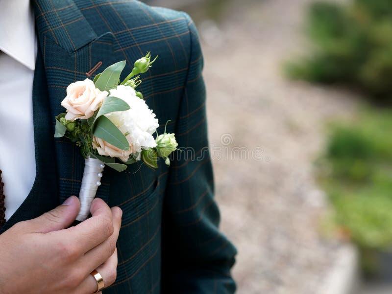 新郎的婚姻的钮扣眼上插的花 库存图片
