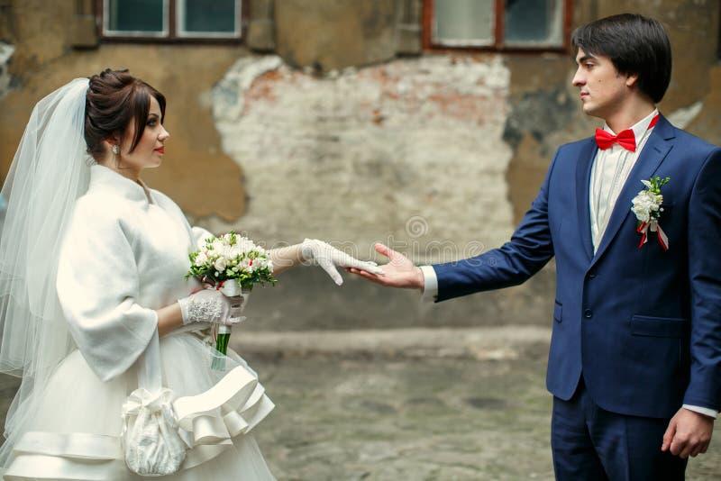 新郎看充满爱握她的在一白色glov的新娘胳膊 库存照片
