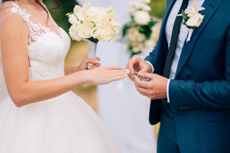 新郎穿戴在新娘的手指的一个圆环在婚礼 免版税库存图片