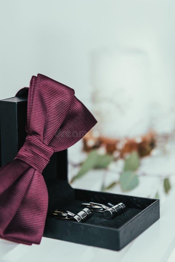 新郎选择聚焦蝶形领结和袖口在箱子 免版税库存照片