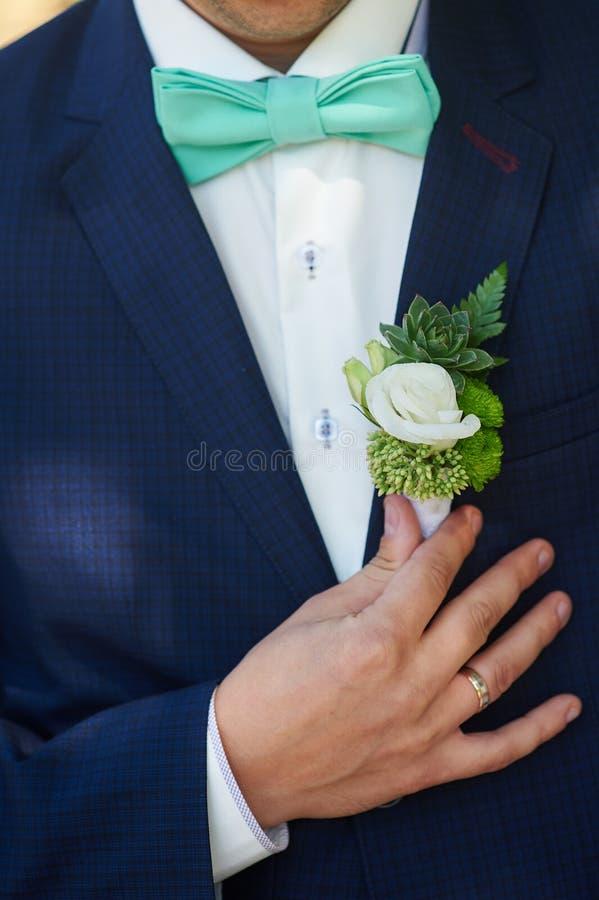 新郎钮扣眼上插的花调整他的在夹克口袋的手 库存照片