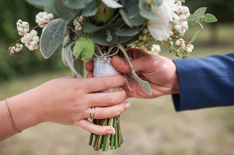 新郎给新娘一个婚礼花束特写镜头 库存照片