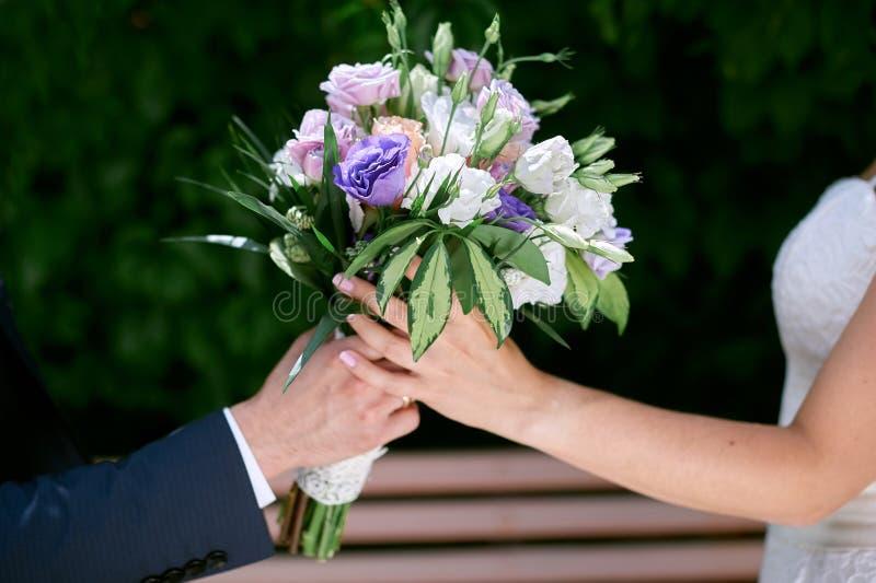 新郎给新娘婚礼花束 免版税图库摄影