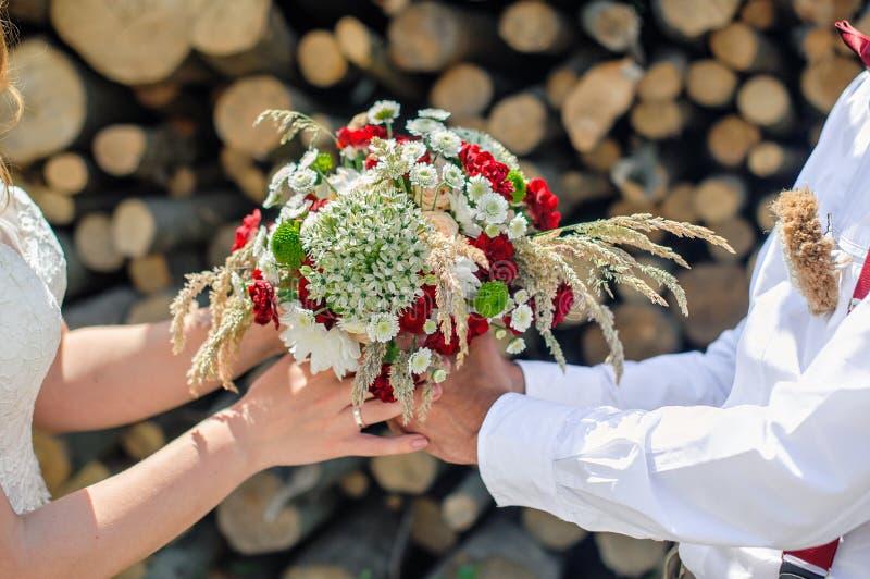 新郎给新娘美丽的婚礼花束 图库摄影