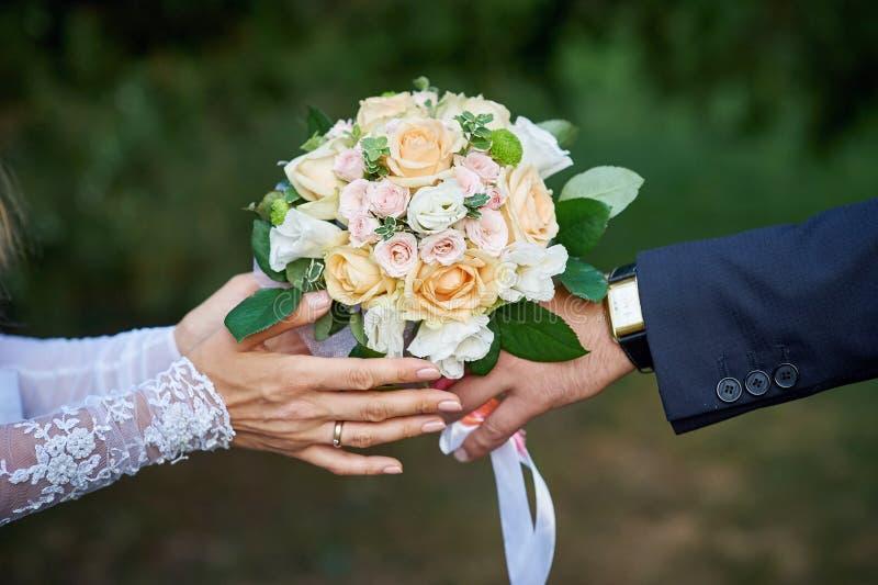 新郎给新娘美丽的婚礼花束 免版税库存图片