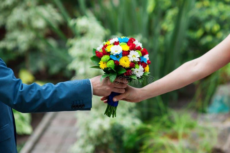 新郎给新娘美丽的婚礼花束 免版税库存照片