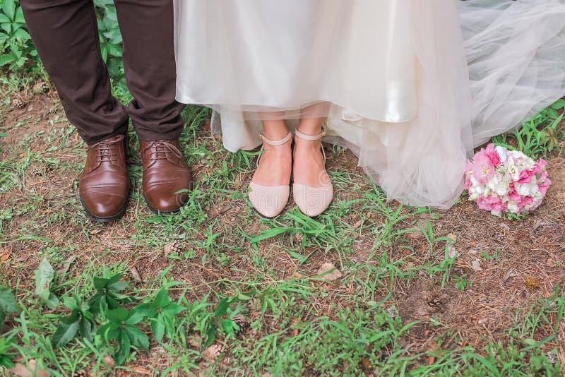 新郎` s和新娘` s的逗人喜爱的播种的图片在草一起穿上鞋子身分 图库摄影