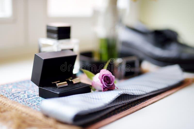 新郎` s婚礼辅助部件:栓和在黑匣子的两个金黄袖扣 免版税图库摄影