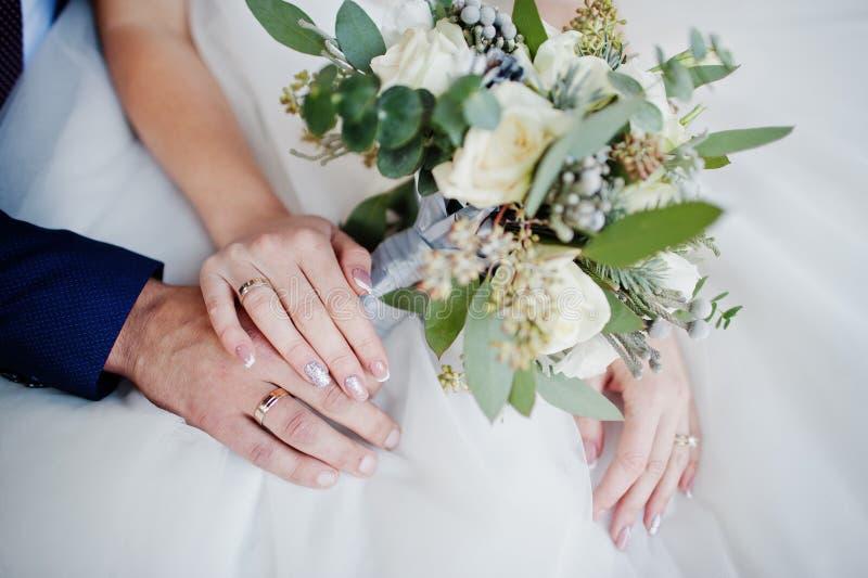 新郎` s特写镜头照片和新娘有圆环和bouqu的` s手 免版税库存照片