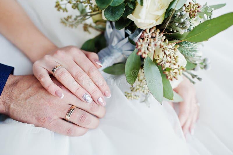 新郎` s特写镜头照片和新娘有圆环和bouqu的` s手 免版税库存图片