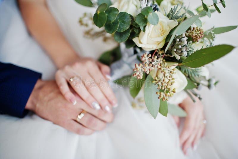 新郎` s特写镜头照片和新娘有圆环和bouqu的` s手 库存照片