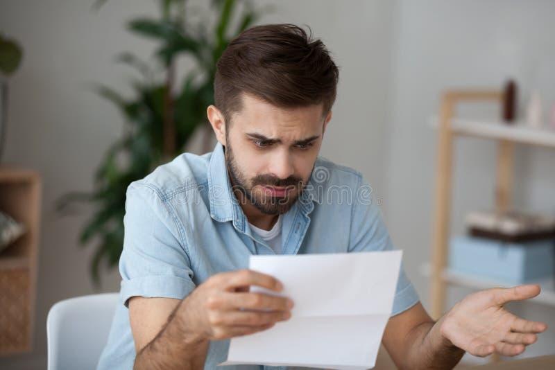 新闻冲击的被混淆的男性读的信件 免版税库存照片