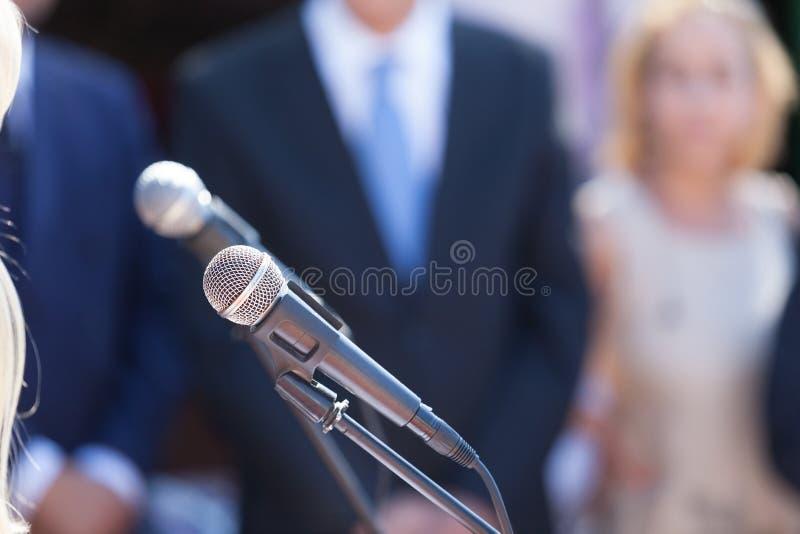 新闻发布会 话筒在反对被弄脏的观众的焦点 库存图片