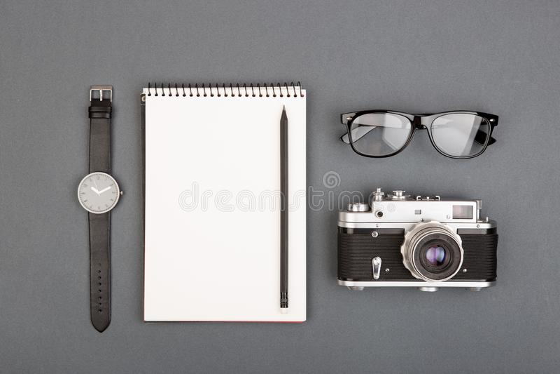 新闻工作者或博客作者桌-螺旋空白的笔记本、铅笔、照相机和玻璃在灰色背景,顶视图 免版税库存照片