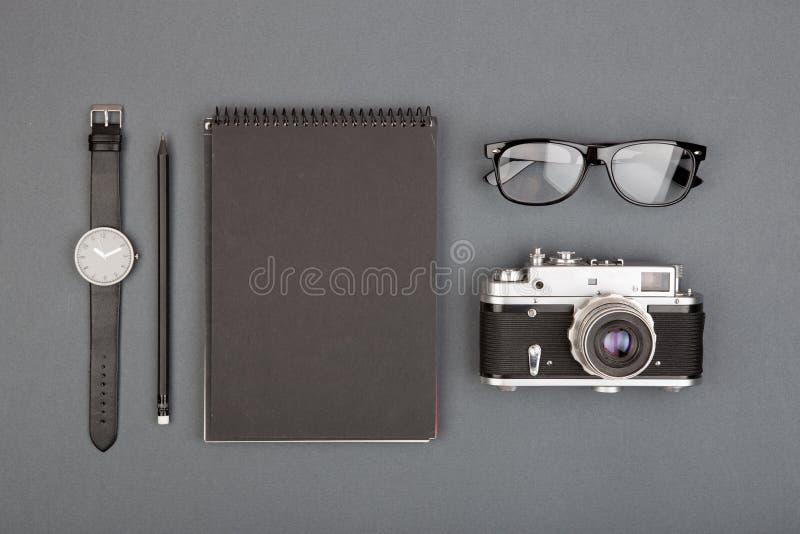 新闻工作者或博客作者桌-螺旋空白的笔记本、铅笔、照相机和玻璃在灰色背景,顶视图 图库摄影