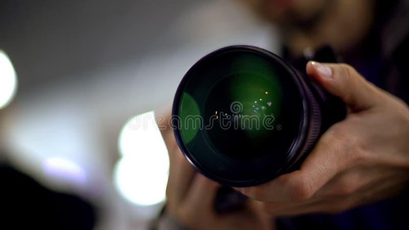 新闻工作者采取报告的藏品照相机射击,暗中侦察在名人的无固定职业的摄影师 免版税图库摄影
