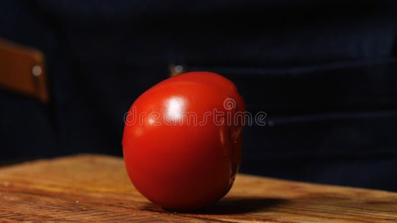 新鲜和成熟蕃茄和在背景的被弄脏的厨师形象特写镜头在木板的 E ?? 免版税库存图片