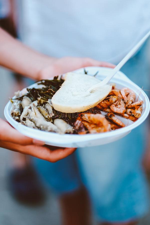 新鲜和油煎的海鲜用虾、沙丁鱼鱼在一块板材用绿色菜沙拉和面包 库存照片