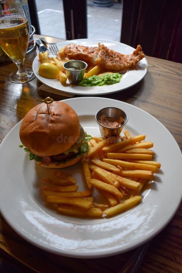 新鲜和鲜美牛肉汉堡和英国传统炸鱼加炸土豆片 免版税库存照片