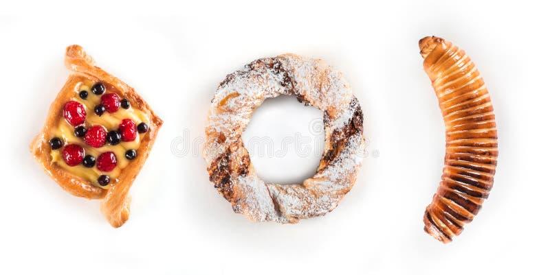 新鲜和鲜美莓果蛋糕、一个椒盐脆饼与糖粉末和香蕉在面团被隔绝在白色背景 免版税库存照片
